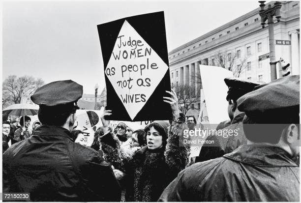 A young American woman holds up a sign as she protests for women's rights in front of the Federal Trade Commission headquarters while policemen look...
