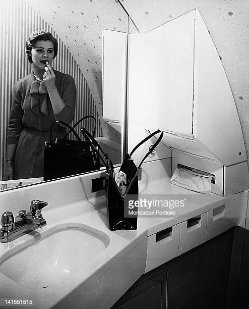 A young American woman is putting on lipstick in front of the mirror in the bathroom on board a Boeing 707 120 Stratoliner plane USA 1950s