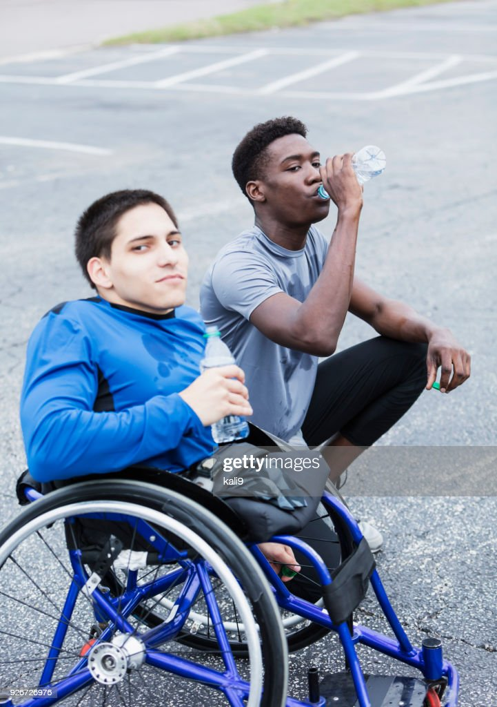 Young amputee and friend, athletes taking break : Stock Photo
