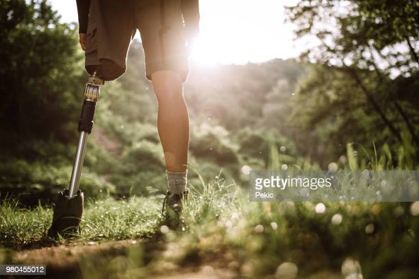 young amputee man spending leisure time in nature - amputee stock pictures, royalty-free photos & images