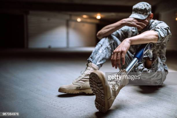 Young Amputee Soldier Crying In Bunker