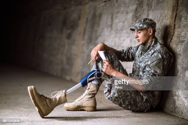 young amputee soldier sitting in bunker alone - injured soldier stock photos and pictures