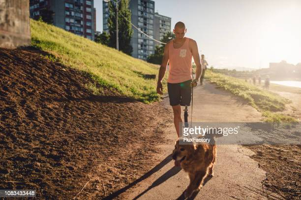 jovens amputados passeando com um cachorro pelo rio - perna humana - fotografias e filmes do acervo