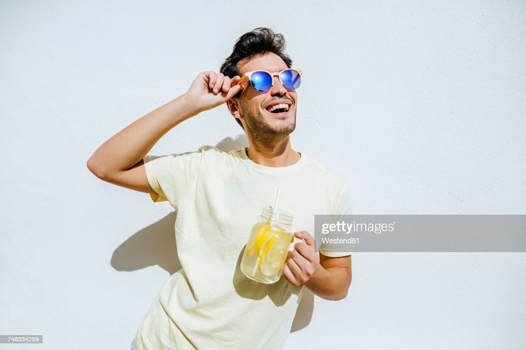 Young an with sunglasses and lemonade in front white wall : Foto de stock