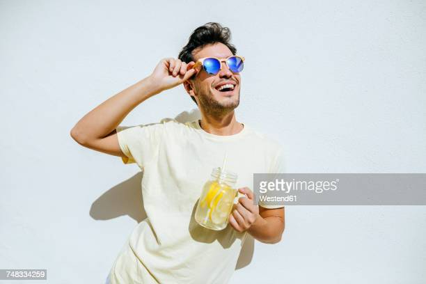 young an with sunglasses and lemonade in front white wall - サングラス 男性 ストックフォトと画像