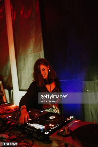 young and attractive female deejay enjoys her music - arte, cultura e espetáculo - fotografias e filmes do acervo