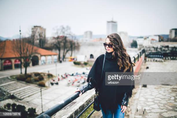 young and attractive woman enjoying a walk in the beautiful day. - poncho stock pictures, royalty-free photos & images