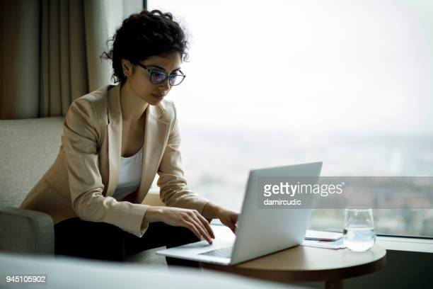 young and beautiful businesswoman working on laptop in a hotel room - business travel stock pictures, royalty-free photos & images