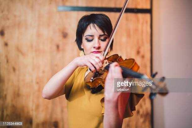 young and beautiful woman artist playing the violin on the stage. - violin family stock photos and pictures