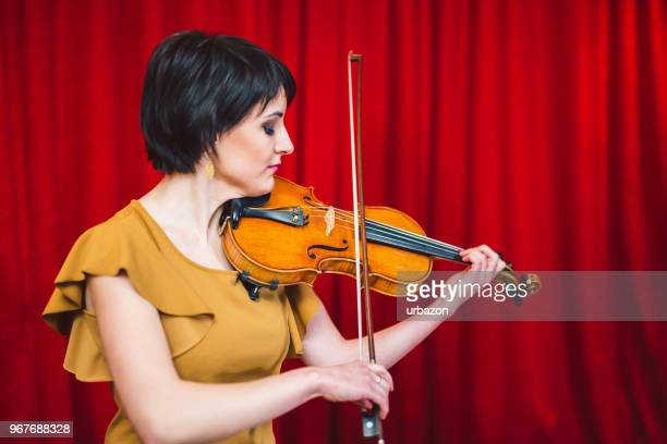 young and beautiful woman artist playing the violin on the stage. - soloist stock photos and pictures