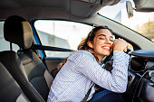 Young and cheerful woman enjoying new car hugging steering wheel sitting inside