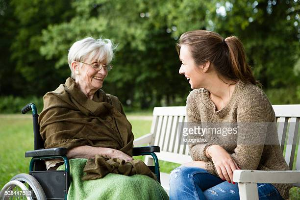 young and disabled senior woman have a talk in park - simple living stock pictures, royalty-free photos & images