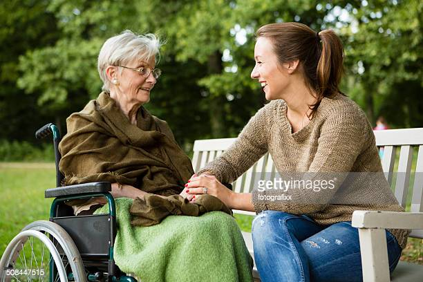young and disabled senior woman have a talk in park