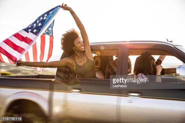 young and fresh group of friends enjoying a road trip journey and freedom in a country road - independence day stock pictures, royalty-free photos & images