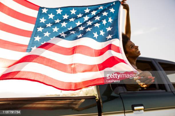 young and fresh group of friends enjoying a road trip journey and freedom in a country road - fourth of july stock photos and pictures