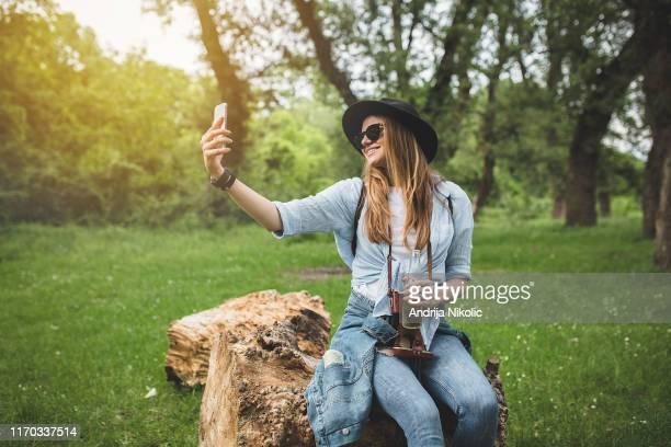 自然の中で自分撮りを取る若くて幸せな美しい女性 - ダブルデニム ストックフォトと画像