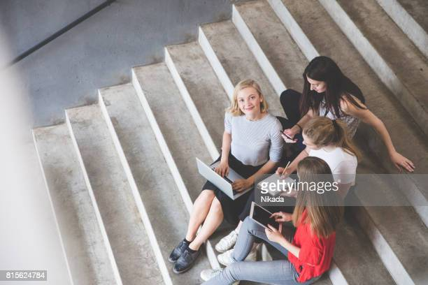 Young and happy urban people holding technologies while sitting on steps
