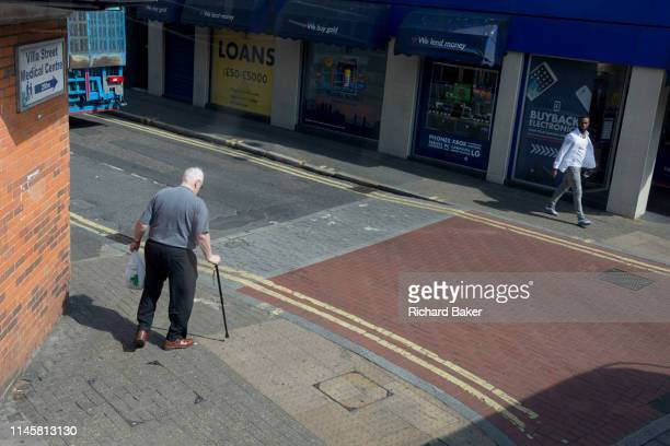 A young and healthy black man strides along the street and an infirm elderly man using a walking stick prepares to carefully cross the road on 22nd...