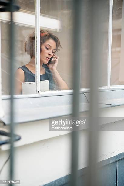 Junge und moderne business-Frau auf Handy durch Fenster.