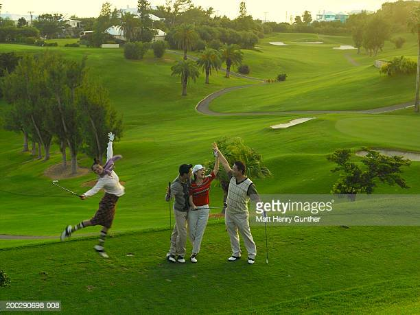Young and mature couples celebrating on golf course (blurred motion)