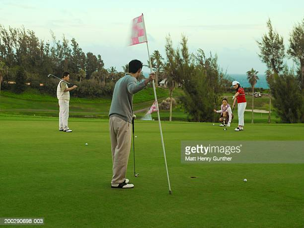 young and mature couples playing golf, mature woman giving pointers - four people stock pictures, royalty-free photos & images