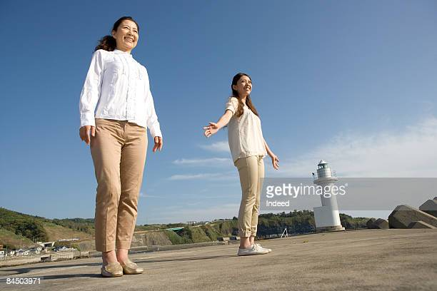 Young and mature woman standing on pier, smiling