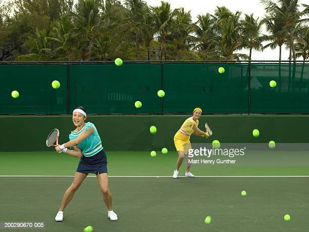 Young and mature women swinging at tennis balls (blurred motion)