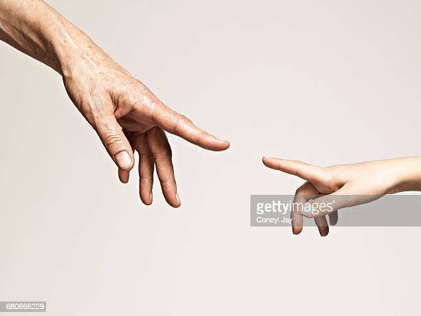 young and old hands point together - touching stock pictures, royalty-free photos & images