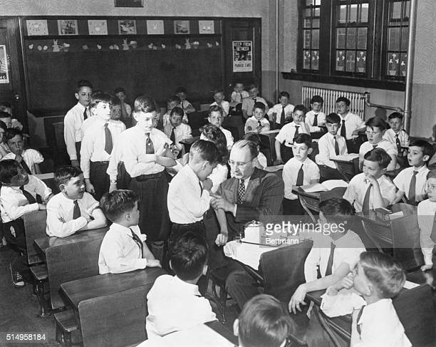 Young and Old Vaccinated to Stem Small Pox Epidemic. New York: Dr. George Long, vaccinates little Patrick Hogan, while other children in the class...
