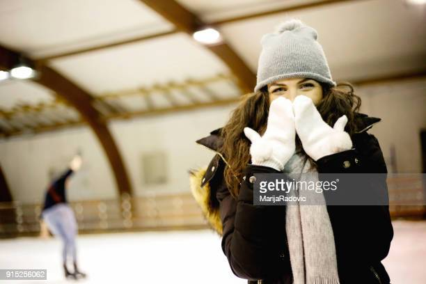 Young and pretty girl skating on indoor ice-rink