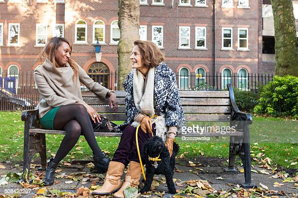young and senior woman in a park (london uk) - bench stock pictures, royalty-free photos & images