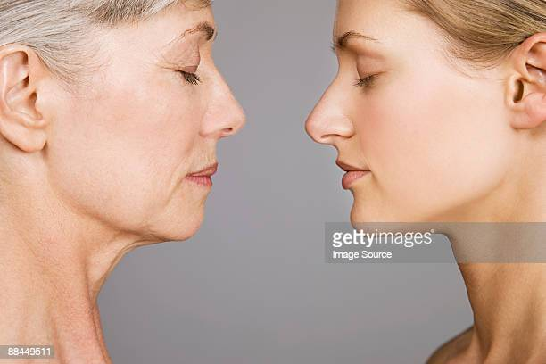 young and senior women face to face - aging process stock pictures, royalty-free photos & images