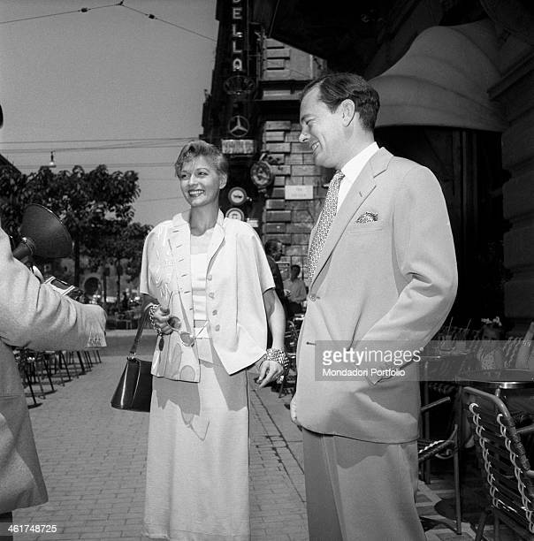 A young and smiling couple meets a photographer during a stroll in the city they are the revue actress Isa Barzizza wellknown for her movies with...