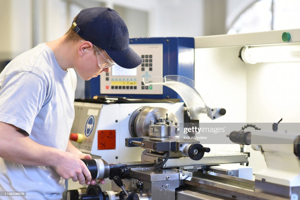young apprentice in vocational training working on a turning machine in the industry : Stock Photo