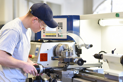 young apprentice in vocational training working on a turning machine in the industry 1148208976