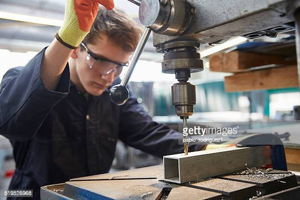 young apprentice using pillar drill in steel fabrication factory - metallic stock photos and pictures