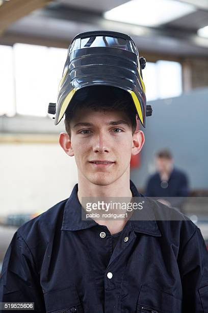 Junge Lehrling mit Gesichtsmaske in Stahl Material Fabrik