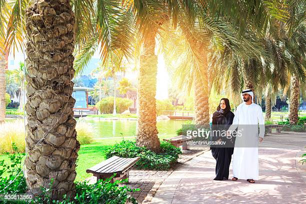 Young Arab couple walking in the park with palms