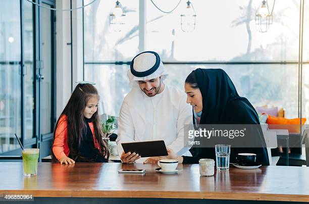 Young Arab family enjoying with tablet pc at cafe
