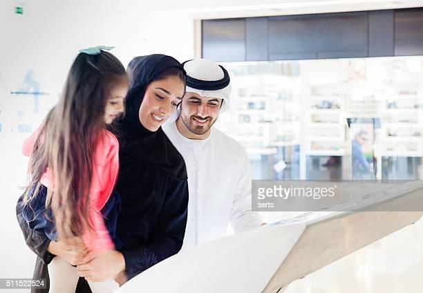 Young Arab family using information display at mall