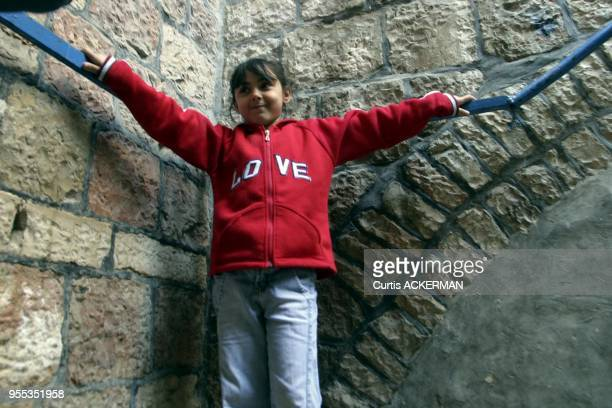 A young Arab girl stands on some steps away from the crowds in the street in the Muslim Quarter of Jerusalem's Old City The Muslim Quarter derives...