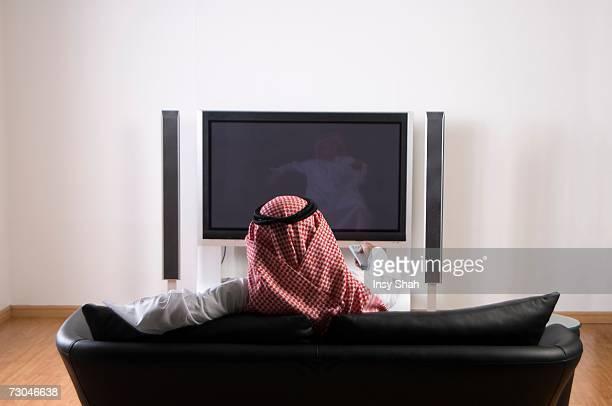 Young Arab man watching TV