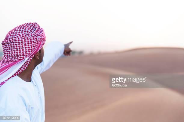 joven árabe permanente sobre dunas de arena y con el objetivo de una dirección. - pañuelo de cabeza fotografías e imágenes de stock