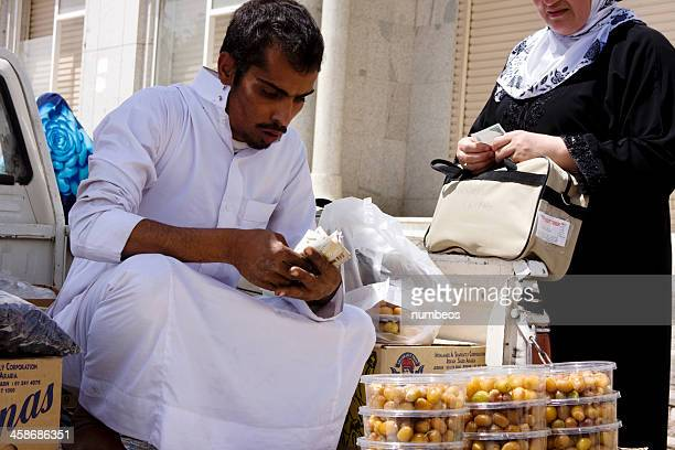 young arab vendor in traditional dress - al madinah stock photos and pictures
