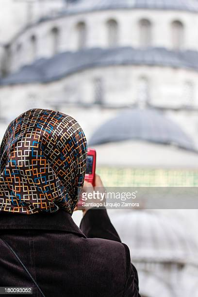 CONTENT] Young Arab woman covered on a colorful veil taking a picture with her smartphone of the Blue Mosque Istanbul Marmara Turkey