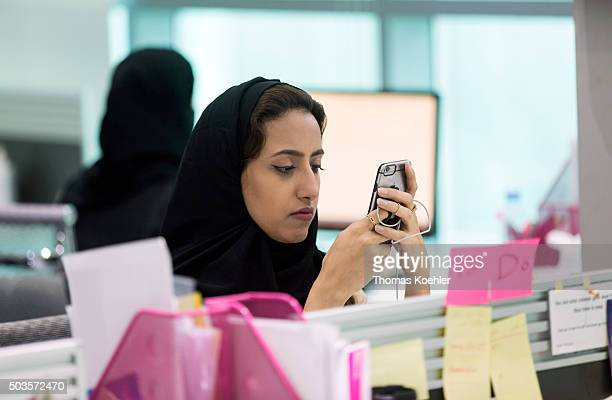 A young Arab woman looking at her smartphone in the employment agency for women 'Glowork' on October 19 2015 in Riad Saudi Arabia