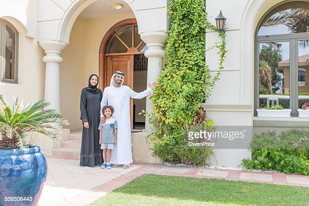 Young Arabic family standing proudly outside their luxury Dubai Villa