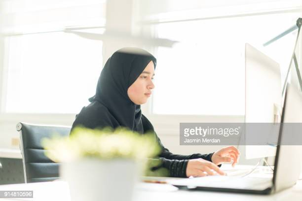 Young Arabic female working in startup office