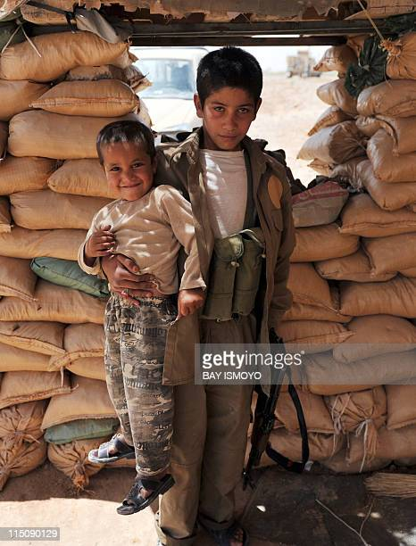 Young Arbaki member Rustam holds his little brother and a weapon as he poses for photographers during the US Marines from Combat Operation Patrol...