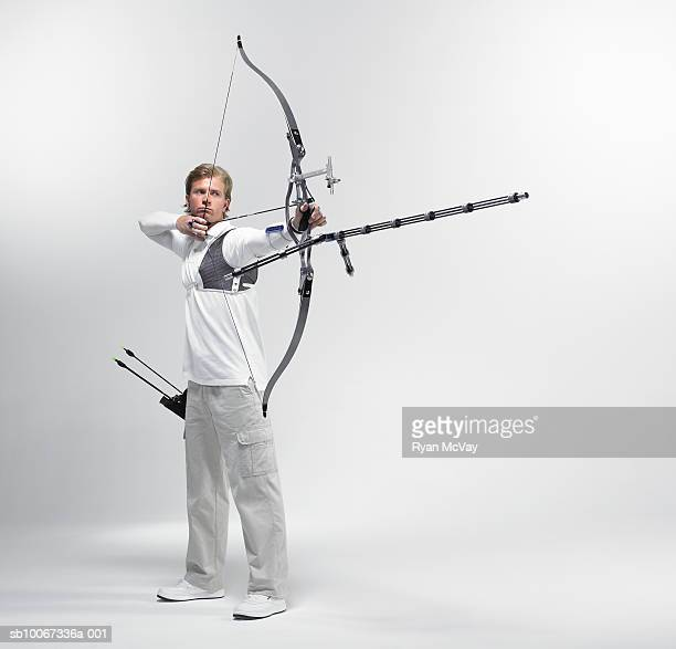 Young archer pointing bow, studio shot